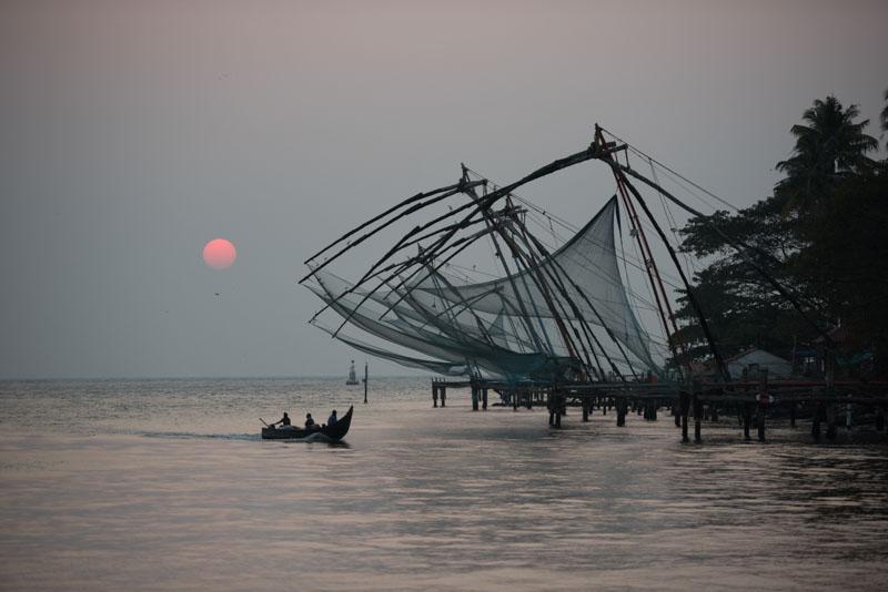 Fishing boat returning at sunset in Kochi, India