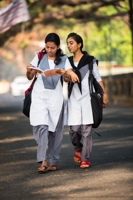 Two girls in uniform on their way to school.